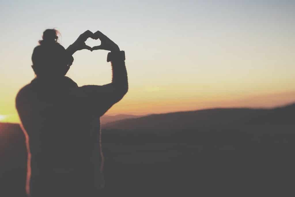 lady with hands in heart shape at sunset